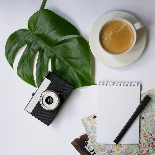 Machen sie sich einen arbeitsplatz mit tropischem palmblatt, notizbuch, kamera, stift, karte und kaffeetasse Premium Fotos