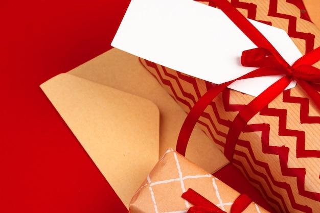 Machen sie weihnachtsgeschenke mit roten bändern auf verziertem weihnachten in handarbeit Premium Fotos