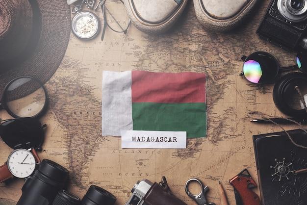 Madagaskar-flagge zwischen dem zubehör des reisenden auf alter weinlese-karte. obenliegender schuss Premium Fotos