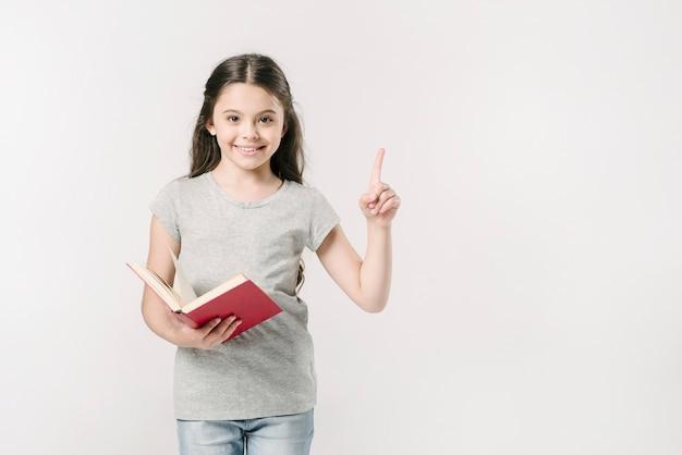 Mädchen, das Buch mit dem angehobenen Finger hält Kostenlose Fotos