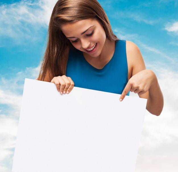 Mädchen hält ein Plakat mit einem Himmel Hintergrund Kostenlose Fotos