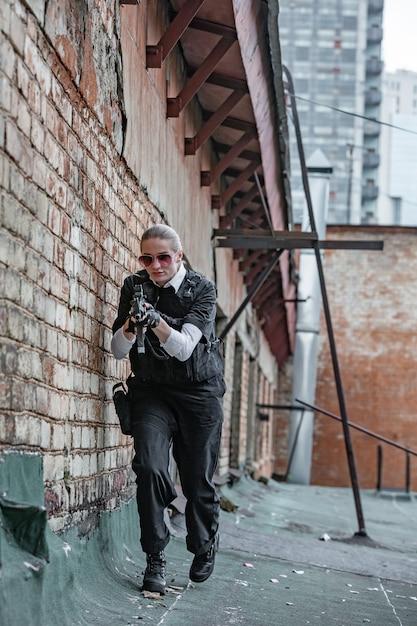 Mächtige frau, die waffe hält. war action movie style Premium Fotos