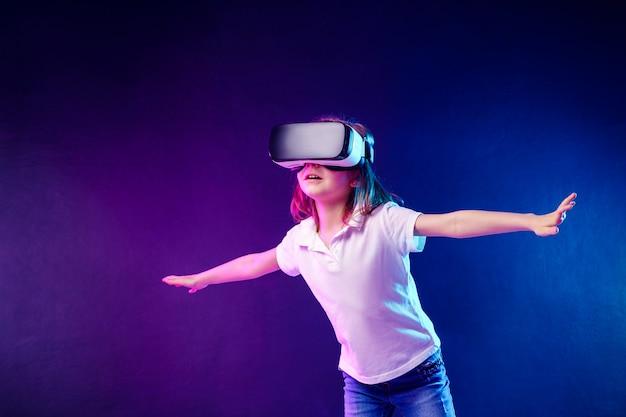 Mädchen 7 yo vr-kopfhörerspiel auf buntem erfahren. kind, das ein spielgerät für virtuelle realität verwendet. Premium Fotos