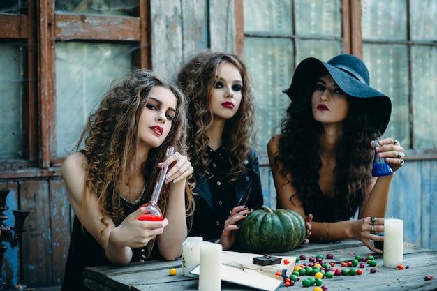 Mädchen als hexen verkleidet mit einem kürbis sitzt an einem tisch und einem roten trank und andere blau Kostenlose Fotos
