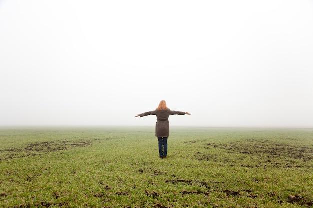 Mädchen am frühlingsfeld in der nebelzeit. Premium Fotos