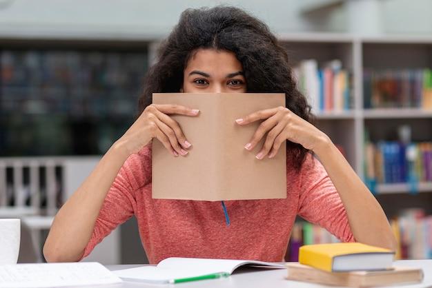 Mädchen an der bibliothek, die gesicht mit buch bedeckt Kostenlose Fotos
