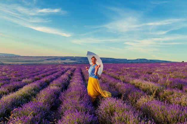 Mädchen auf einem lavendelgebiet bei sonnenuntergang. sonniger sommerabend auf der krim. Premium Fotos