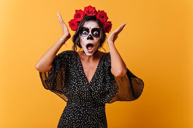 Mädchen aus lateinamerika mit schädel make-up reagiert emotional und posiert für porträt in orange wand Kostenlose Fotos