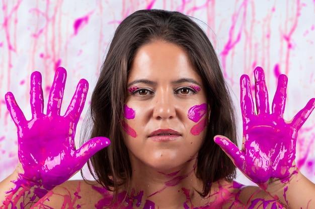 Mädchen bedeckt mit rosa farbe, die spaß hat und frei ist, auf einem konzept, das gegen brustkrebsbewusstsein und frauenbefreiung hilft. Premium Fotos