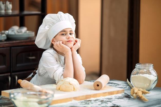 Mädchen bereiten den teig in der küche zu. Premium Fotos