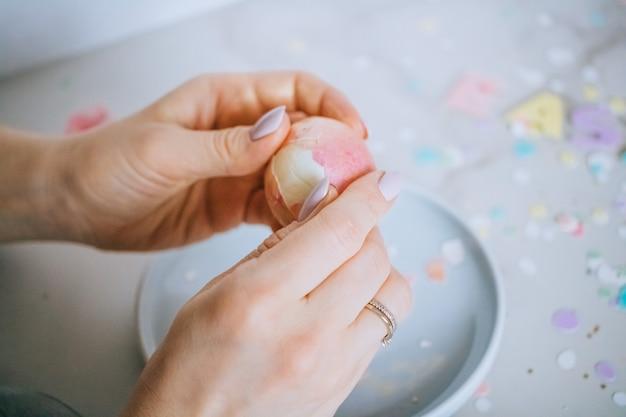 Mädchen bricht goldene ostereier auf marmorhintergrund, konfetti, scheine, bänder. Premium Fotos