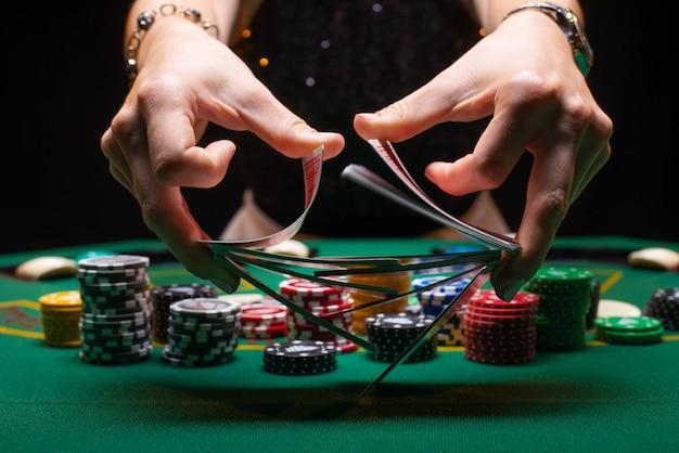 Mädchen croupier mischt pokerkarten in einem casino Premium Fotos