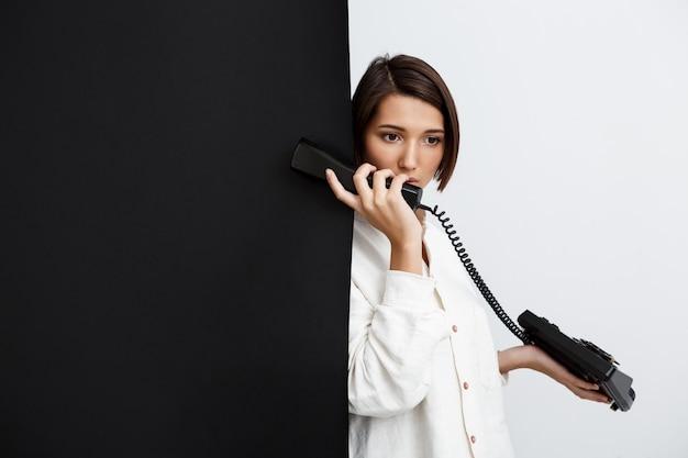 Mädchen, das am alten telefon über schwarzweiss-wand spricht Kostenlose Fotos