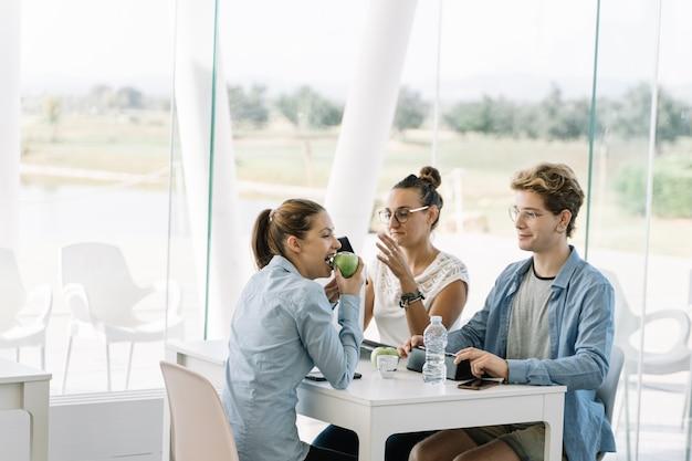 Mädchen, das apfel an einem tisch mit anderen leuten isst Premium Fotos