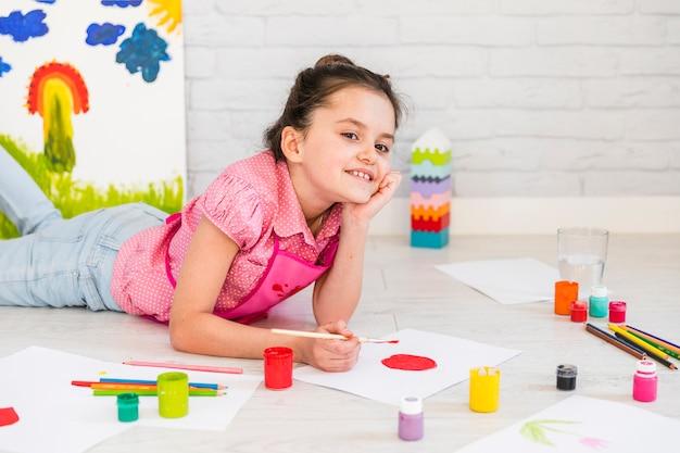 Mädchen, das auf bodenmalerei auf weißbuch mit pinsel liegt Kostenlose Fotos