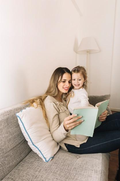 Mädchen, das auf buch beim lesen mit mutter zeigt Kostenlose Fotos