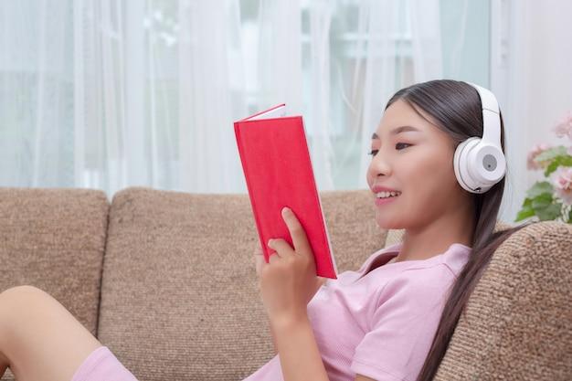 Mädchen, das auf der couch hört musik und liest bücher liegt. Kostenlose Fotos