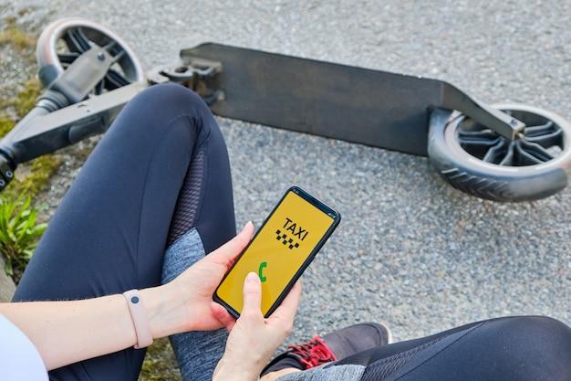 Mädchen, das auf der straße sitzt, ruft ein taxi durch die anwendung auf einem smartphone Premium Fotos