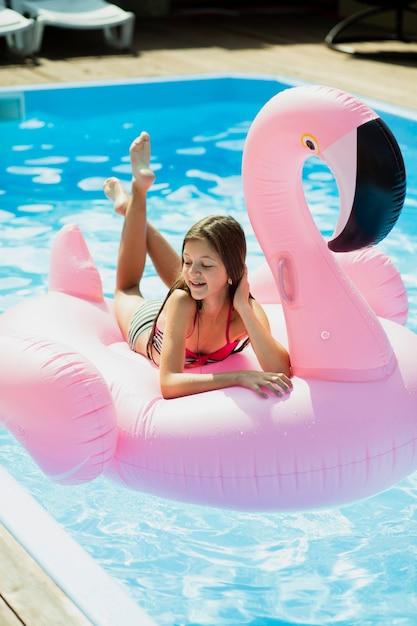 Mädchen, das auf einem flamingo floatie sitzt und unten schaut Kostenlose Fotos