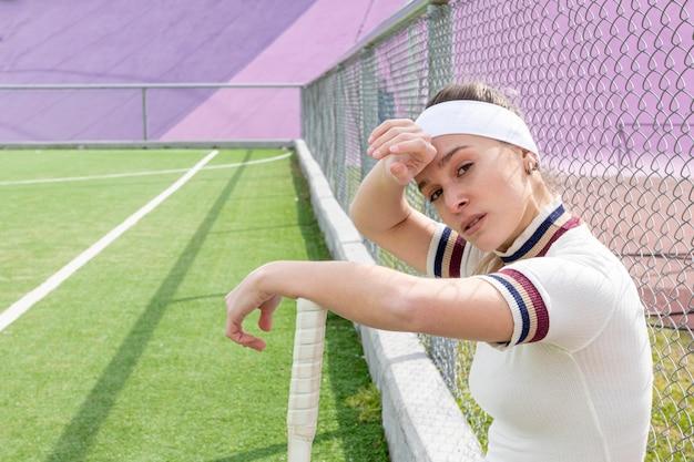 Mädchen, das auf einem tennisfeld schwitzt Kostenlose Fotos