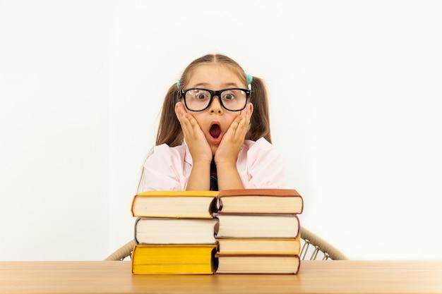 Mädchen, das bei tisch auf weißem hintergrund studiert Premium Fotos