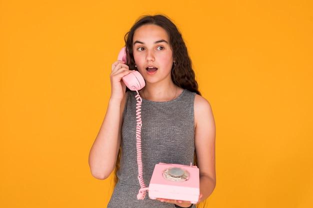 Mädchen, das beim sprechen am telefon entsetzt schaut Kostenlose Fotos