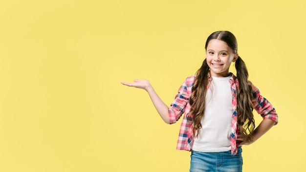 Mädchen, das beiseite mit der hand im studio steht Kostenlose Fotos