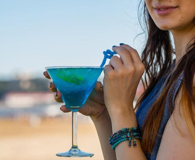 Mädchen, das blaues lagunenalkoholcocktail mit blauen rohren trinkt Kostenlose Fotos