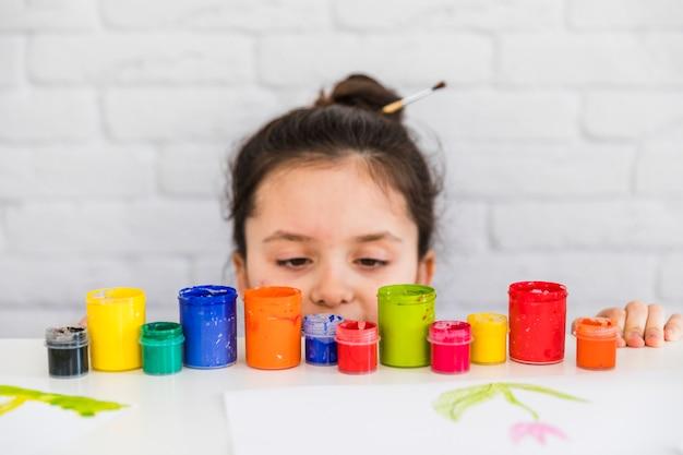 Mädchen, das bunte farbenflaschen am rand der weißen tabelle betrachtet Kostenlose Fotos