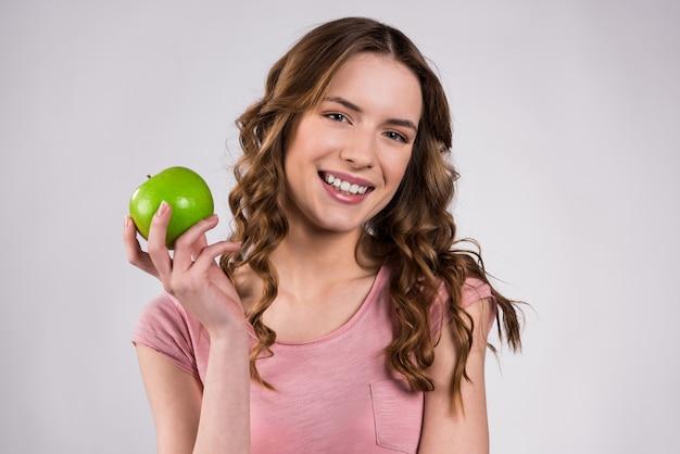 Mädchen, das das lächeln des grünen apfels lokalisiert hält. Premium Fotos