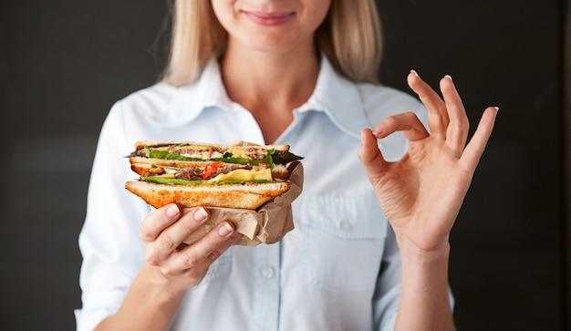 Mädchen, das das ok hält ein sandwich darstellt Premium Fotos