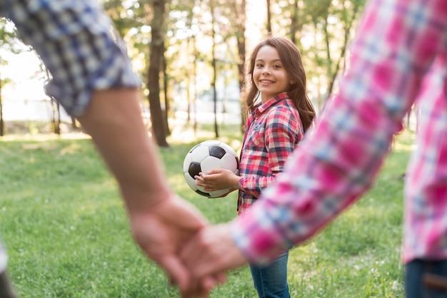 Mädchen, das den fußball betrachtet ihre elternteilholdinghand im park hält Kostenlose Fotos