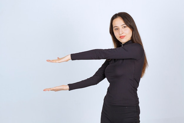 Mädchen, das die geschätzte höhe eines objekts zeigt. Kostenlose Fotos