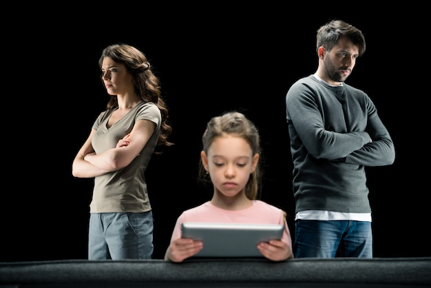 Mädchen, das digitale tablette während eltern stehen mit den gekreuzten armen auf schwarzem verwendet Premium Fotos