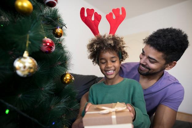 Mädchen, das durch weihnachtsbaum steht und geschenkbox auspackt, die überrascht schaut Kostenlose Fotos