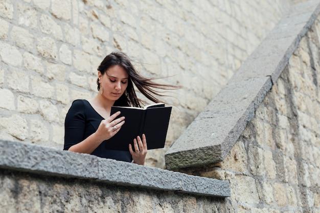 Mädchen, das ein buch an einem windigen tag liest Kostenlose Fotos