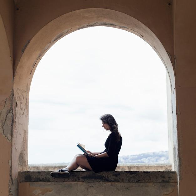Mädchen, das ein buch auf einem fenster liest Kostenlose Fotos