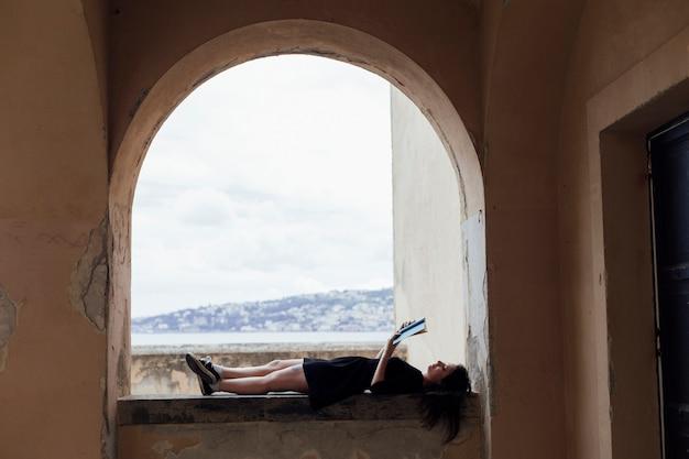 Mädchen, das ein buch auf einer horizontalen lage liest Kostenlose Fotos