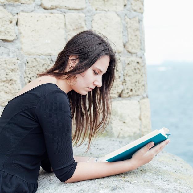 Mädchen, das ein buch in der straße liest Kostenlose Fotos