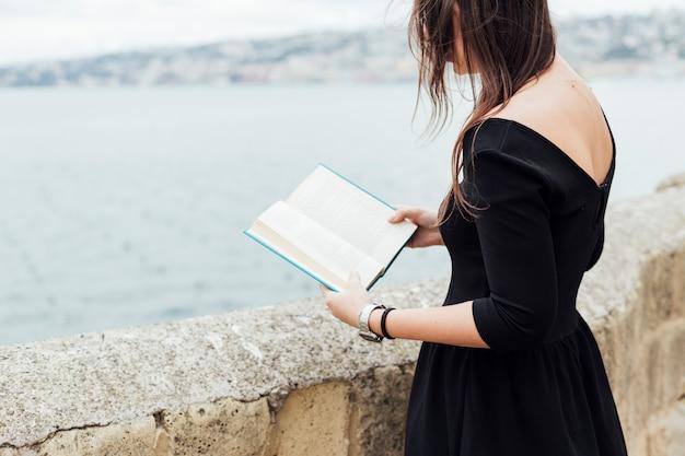 Mädchen, das ein buch nahe dem meer liest Kostenlose Fotos