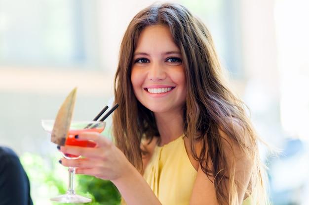 Mädchen, das ein cocktail in einer kneipe hat Premium Fotos