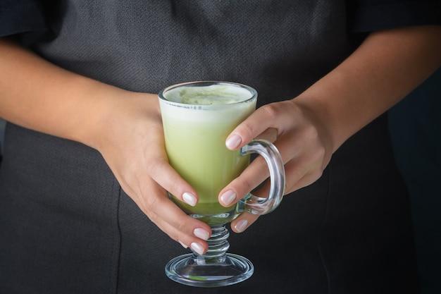 Mädchen, das ein glas mit einem matcha-grüntee-getränk hält. Premium Fotos