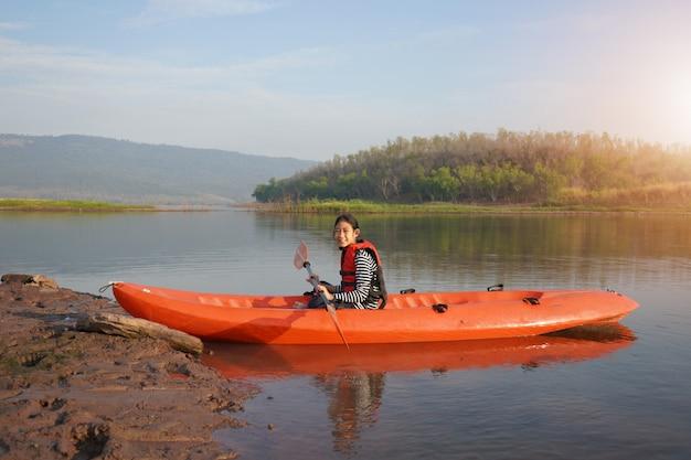 Mädchen, das ein kanu auf ruhigem wasser rudert Premium Fotos