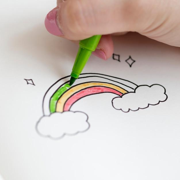 Mädchen, das ein regenbogengekritzel in einem notizbuch färbt Kostenlose Fotos