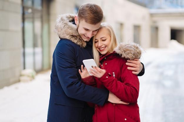 Mädchen, das ein telefon in seiner hand und in ihnen betrachten den smartphone hält. Kostenlose Fotos