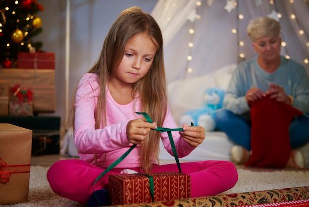 Mädchen, das ein weihnachtsgeschenk verpackt Kostenlose Fotos