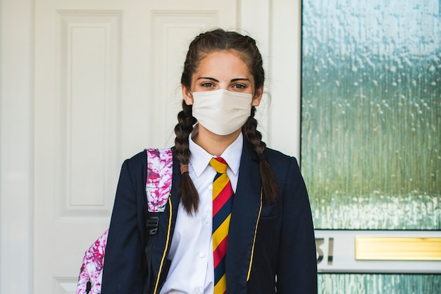 Mädchen, das eine maske trägt und in der neuen normalität zur schule geht Kostenlose Fotos