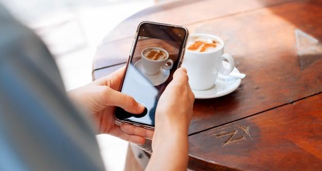 Mädchen, das eine tasse kaffee fotografiert Premium Fotos