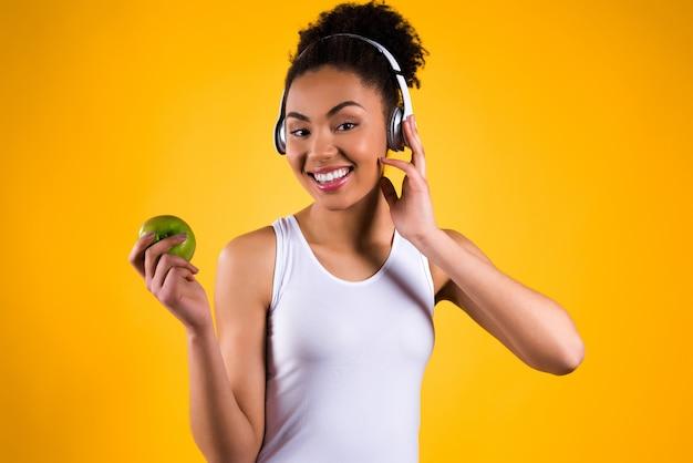 Mädchen, das einen apfel in ihrer hand hält und musik hört Premium Fotos