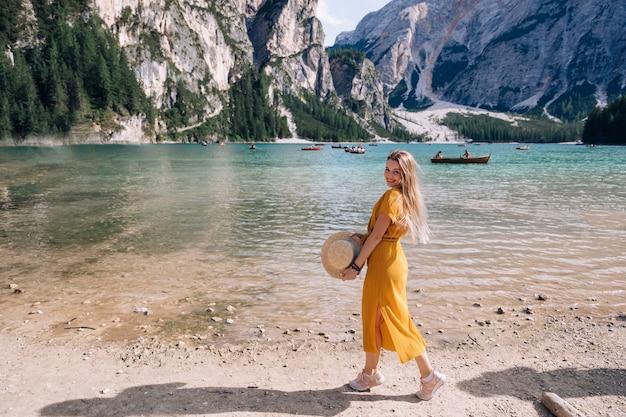 Mädchen, das einen bootsfahrer in ihren händen hält und kamera betrachtet. junge frau, die am ufer des malerischen bergsees aufwirft. dolomiten, italien, europa. Premium Fotos